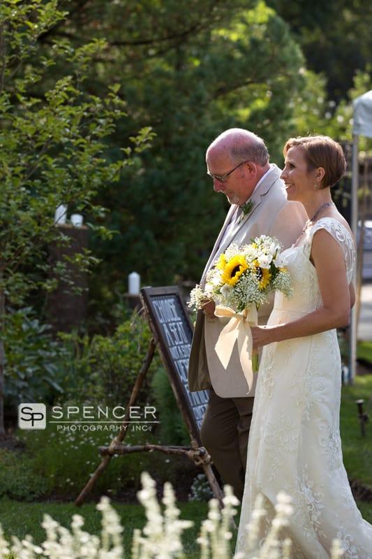 dad walking bride down aisle at green wedding