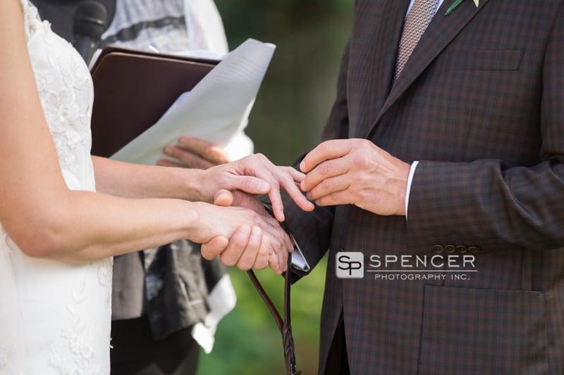 groom putting on brides wedding ring