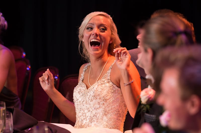 bride laughing at her reception table