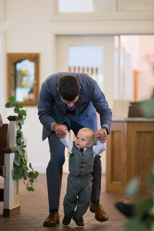 ring bearer being helped down the aisle