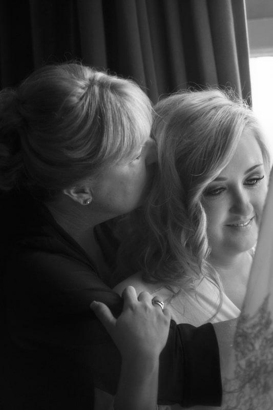 mom kissing bride