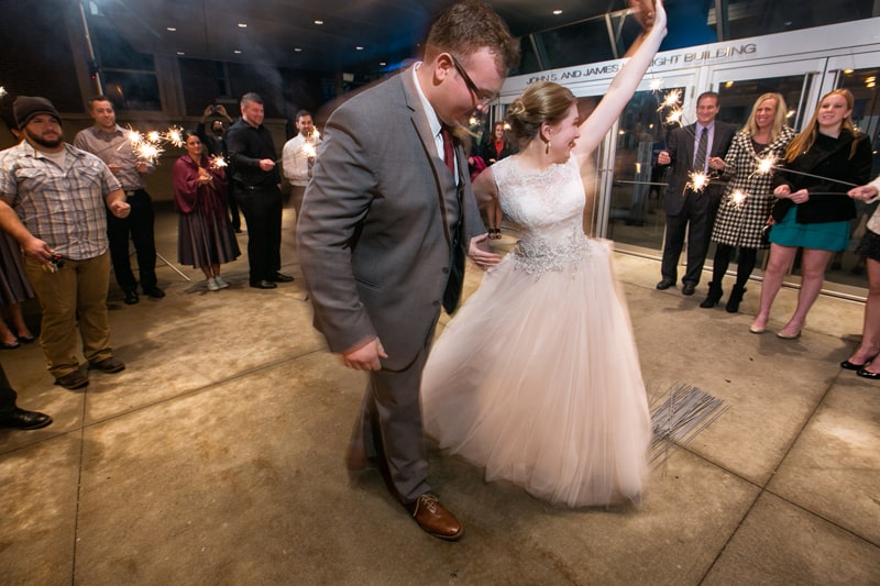 bride and groom exit their wedding reception at akron art museum
