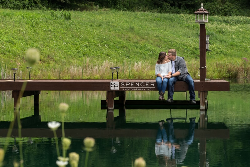 couple kissing on pond dock