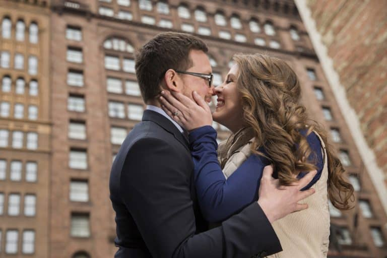 a kiss during their engagement pictures in downtown Clev