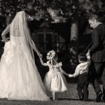 bride and groom walking with flower girl