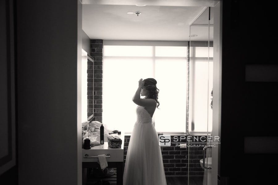 bride fixing her hair on wedding day