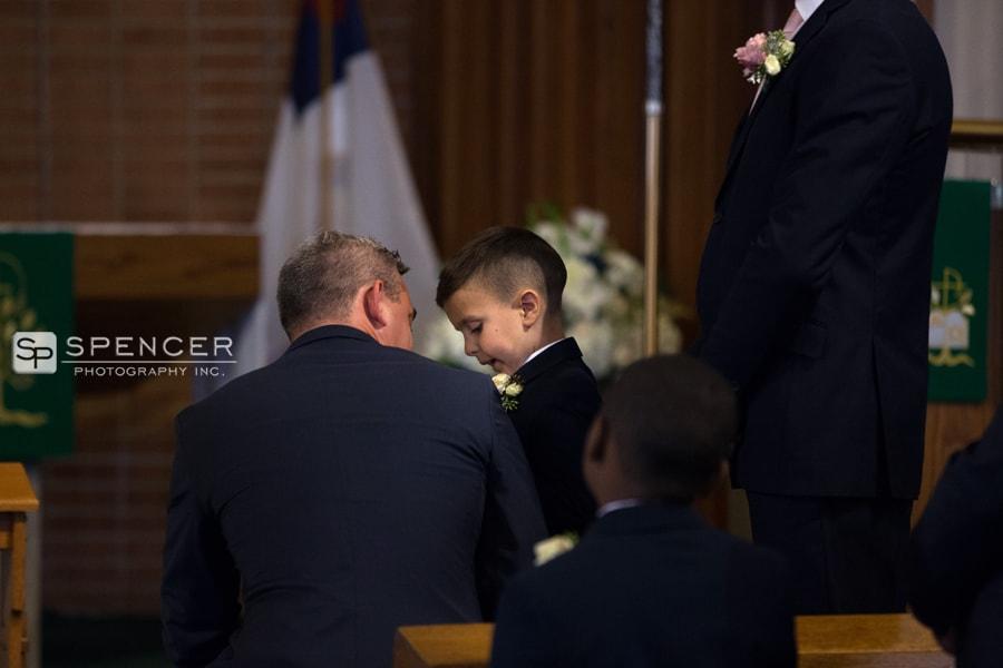 groom talking to brides son at wedding ceremony