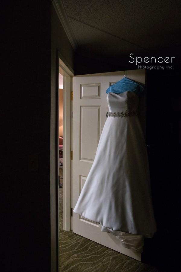 wedding dress haning on door