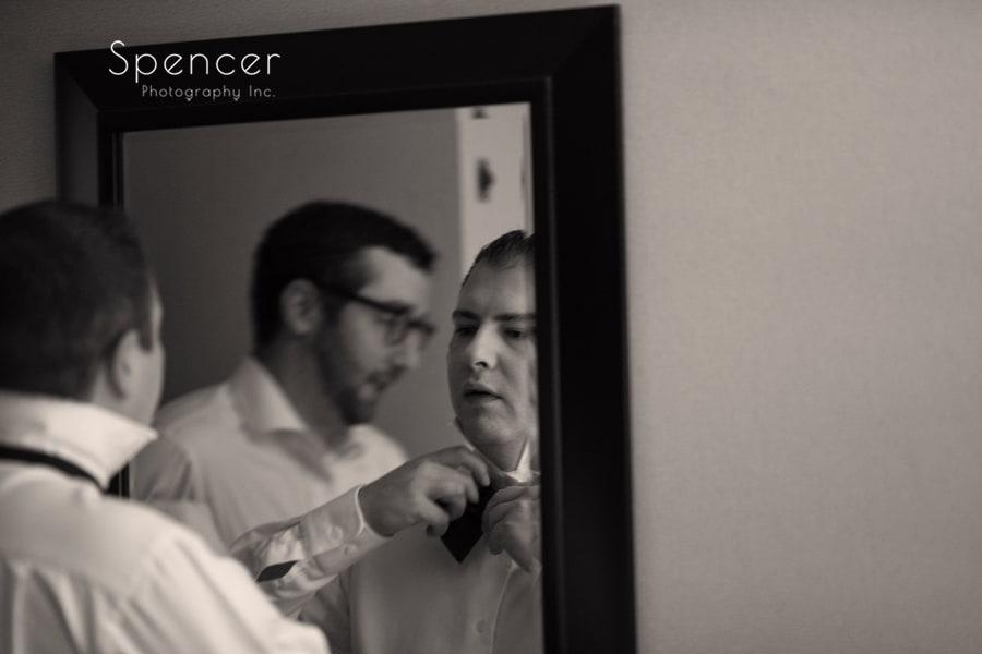 groom attempting to tie his bowtie