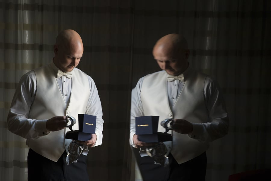 A picture with a reflection of the groom opening his wedding day gift