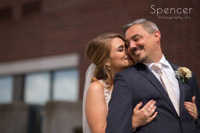 Bride kissing groom before their wedding in akron