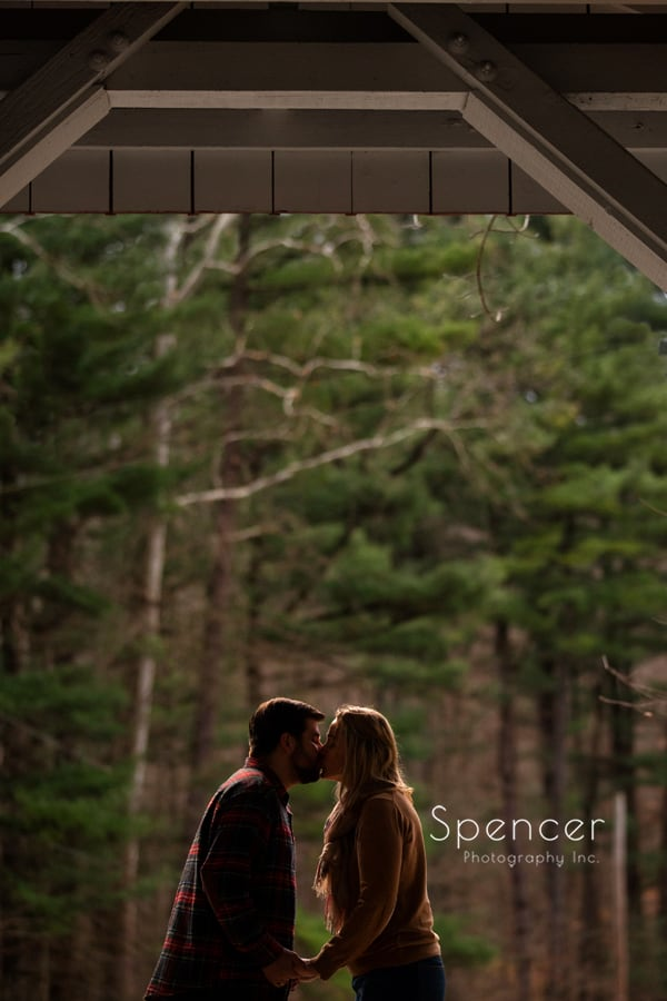Couple kissing under covered bridge