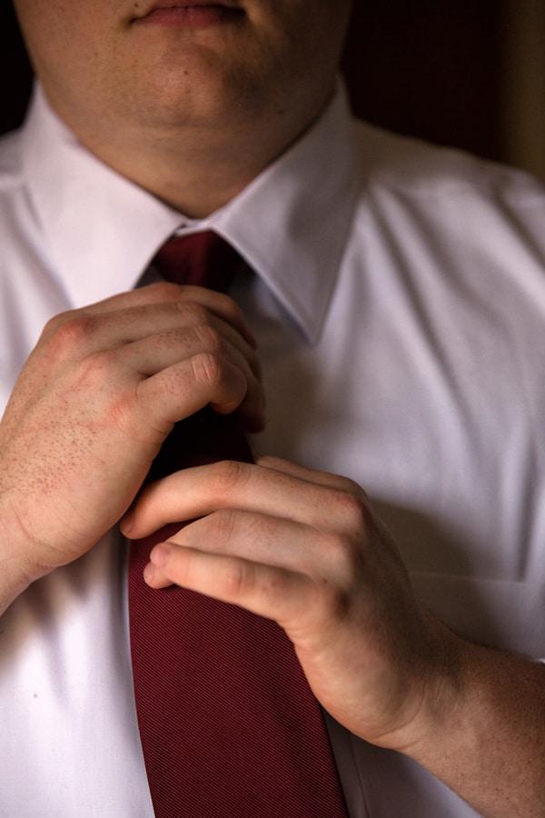 Groom adjusting knot on tie