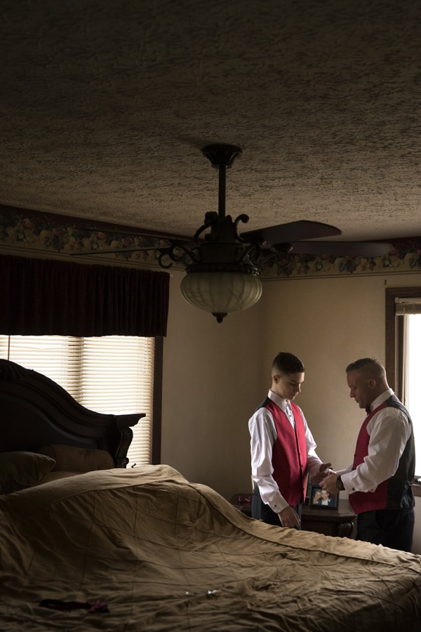 Groom helping his son with his tux