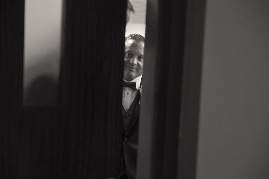 Groom peaks out of chruch door right before ceremony