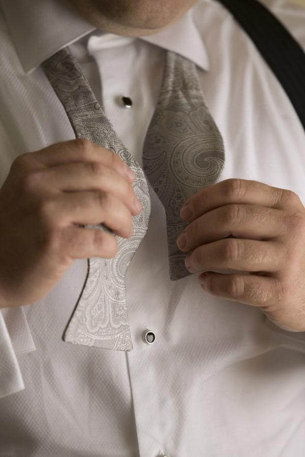 Groom tying his bowtie
