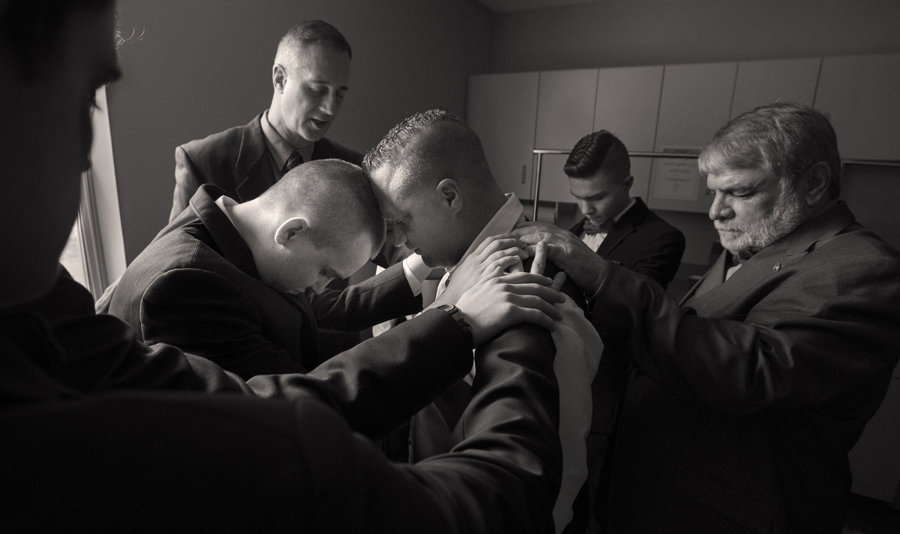 Groomsmen have a moment of prayer before the wedding ceremony