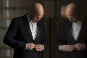 Picture with reflection of groom buttoning his jacket