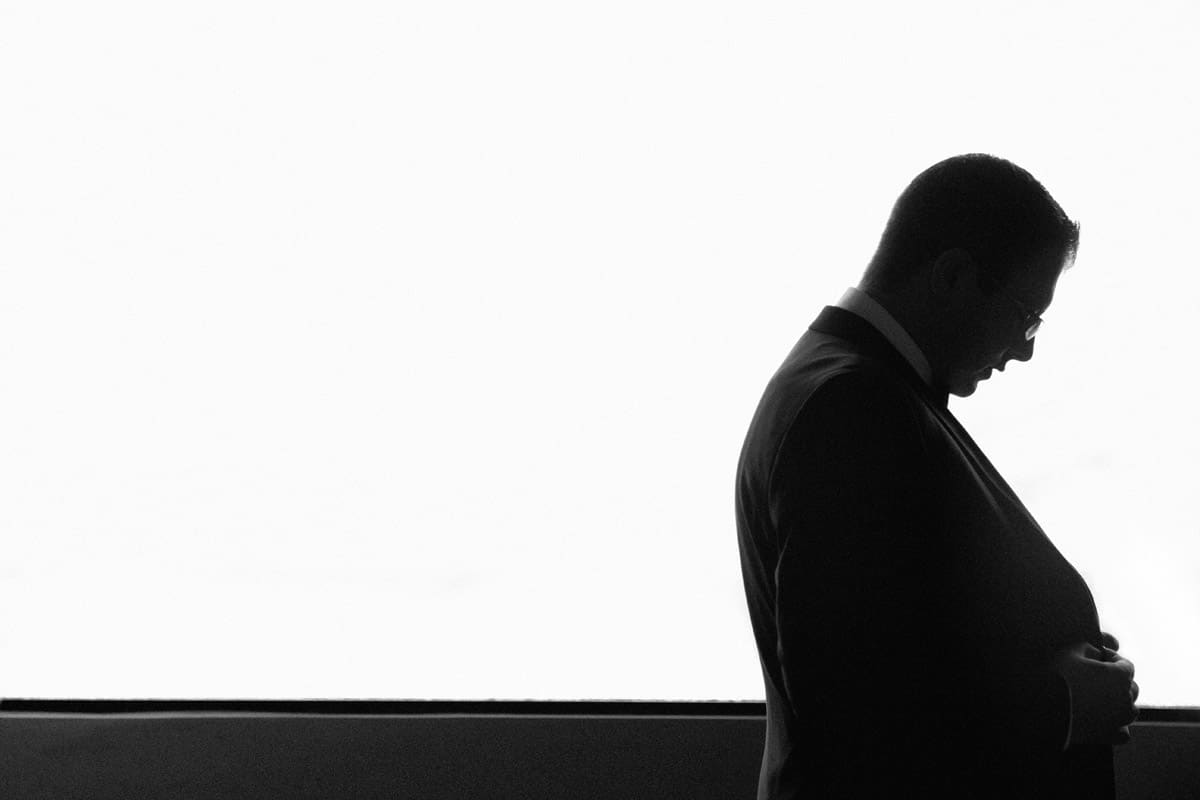 silhouette: groom buttoning his jacket in Cleveland