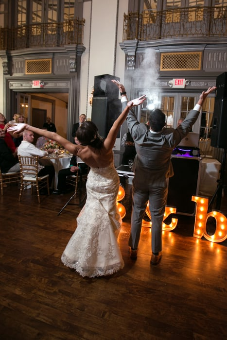 bride and groom throw powder entering their wedding reception at tudor arms