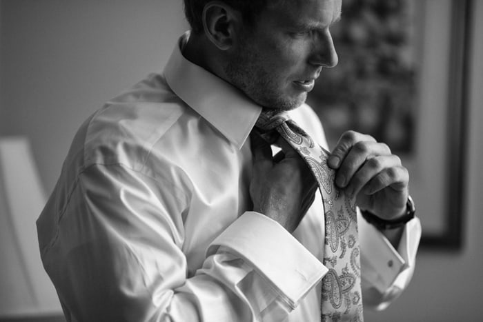 groom getting dressed for wedding at club at hillbrook