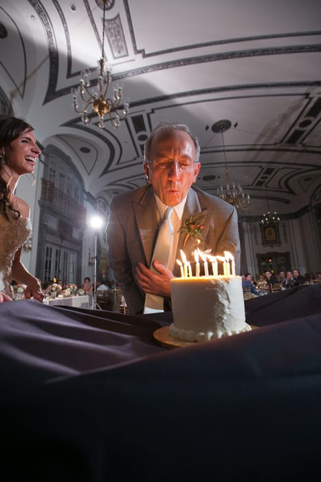 father of bride blows out candles of birthday cake