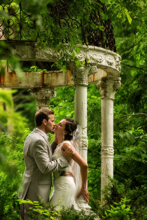 groom kissing bride under gazebo at the Club at Hillbrook