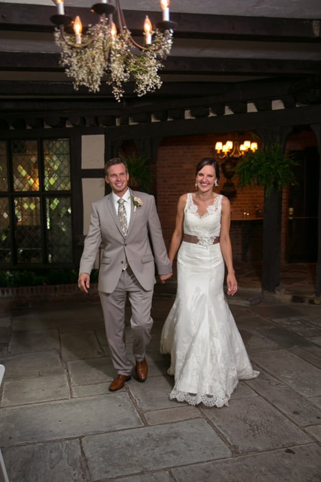 bride and groom enter their wedding reception at the club at hillbrook