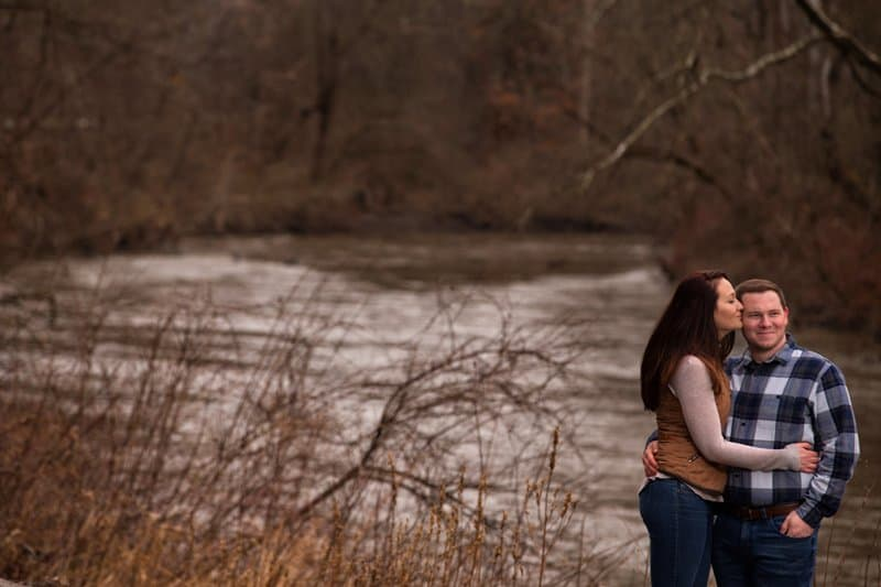couple kissing in outdoor engagement pictures in Akron