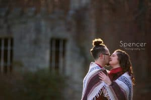 engaged couple kissing in front of squires castle