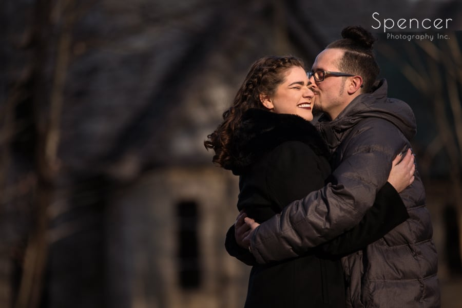 man kissing woman at engagement session at squires castle