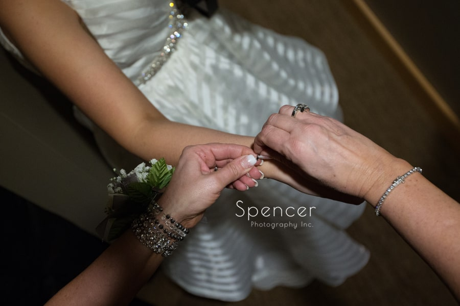 mom helps bride put on bracelet
