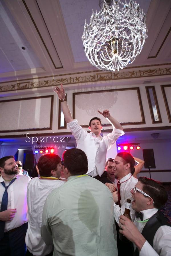 groomsmen pick up groom in ballroom at renaissance reception
