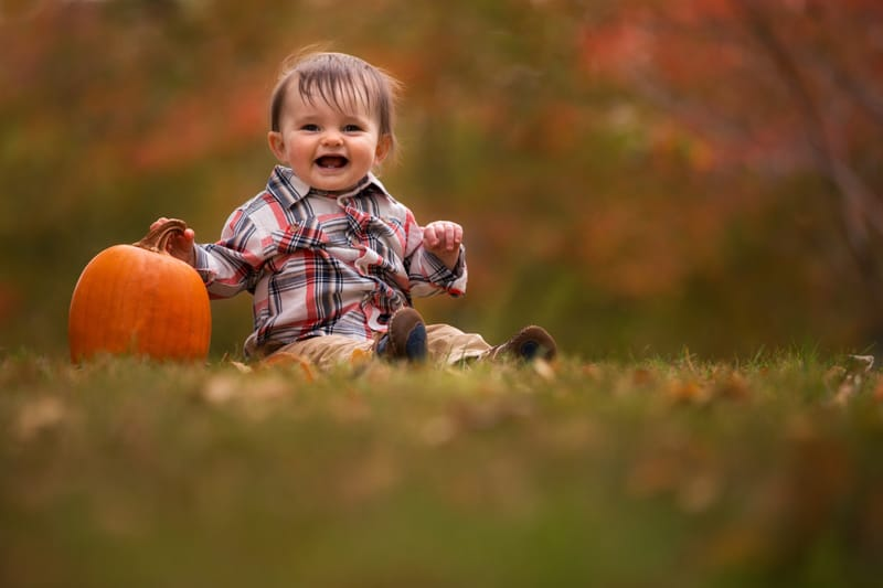 baby with pumpkin laughing