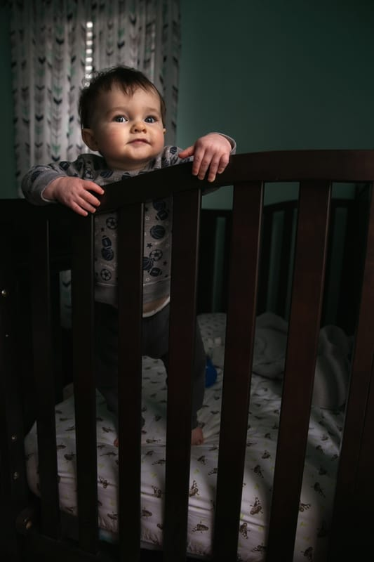 baby looking at camera while standing in crib