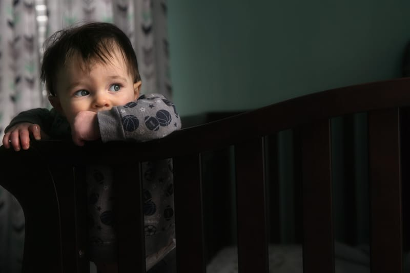 horizontal picture of baby staning in crib