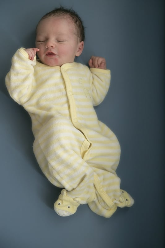 newborn baby in yellow pajamas