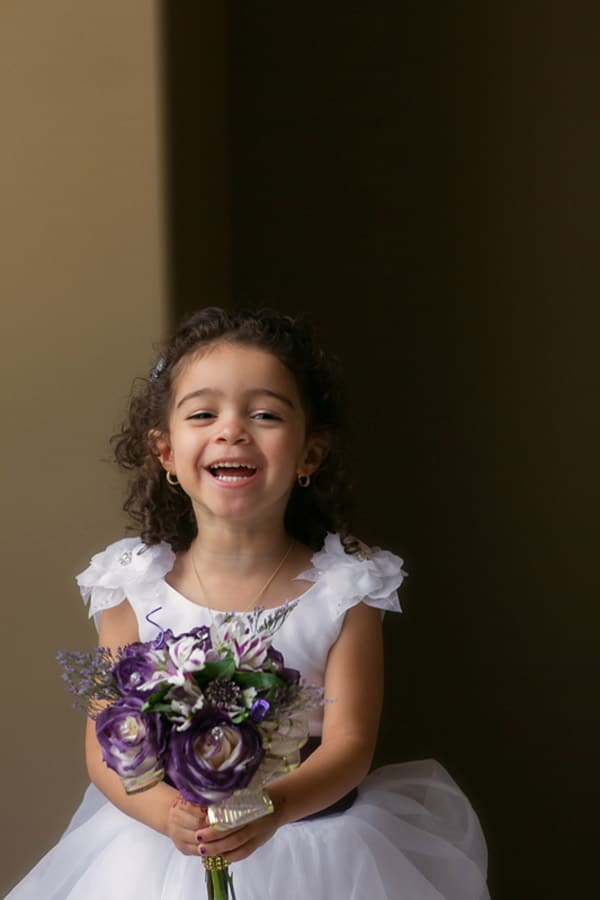 flower girl laughing holding bouquet