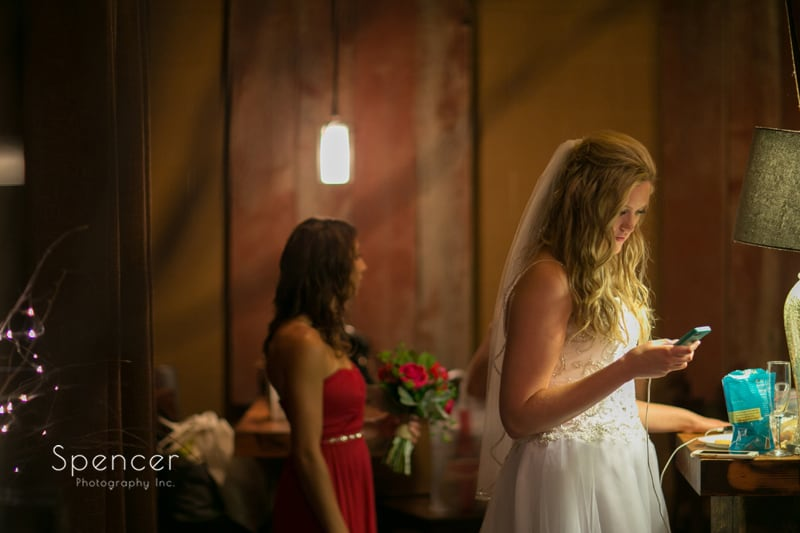 bride checking her phone before wedding at thorncreek winery