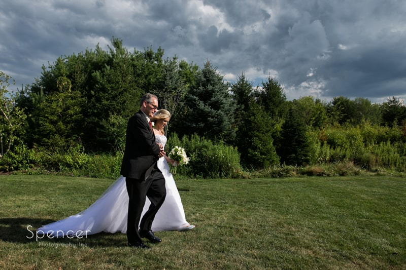 bride and dad walk to wedding ceremony at thorncreek