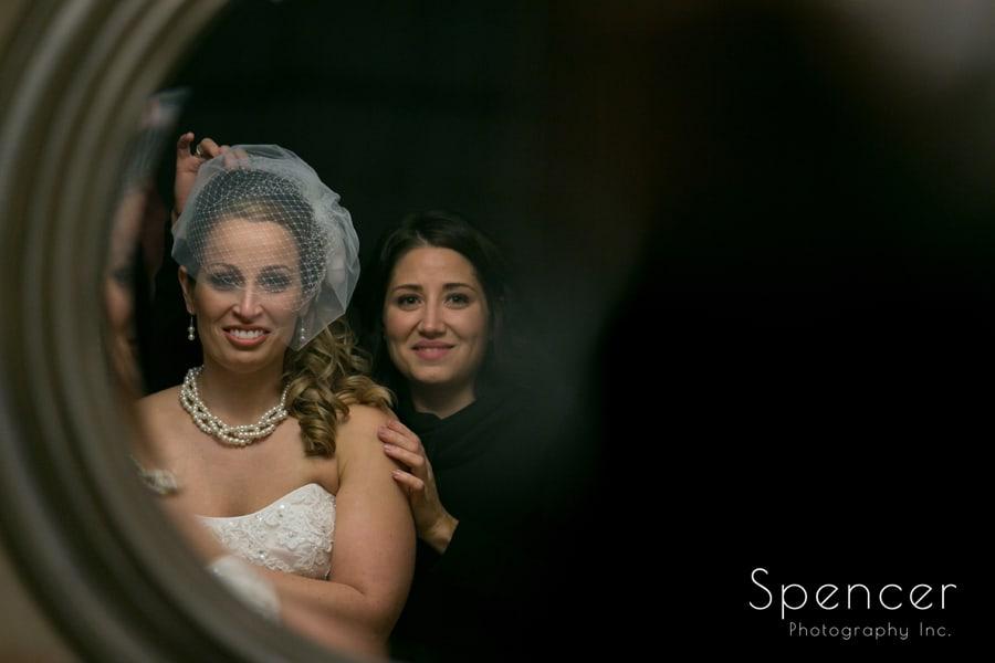 bride looking at wedding veil in mirror