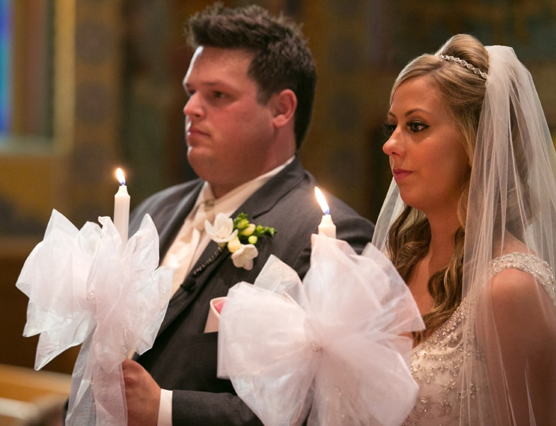 bride and groom holding candles at their wedding ceremony