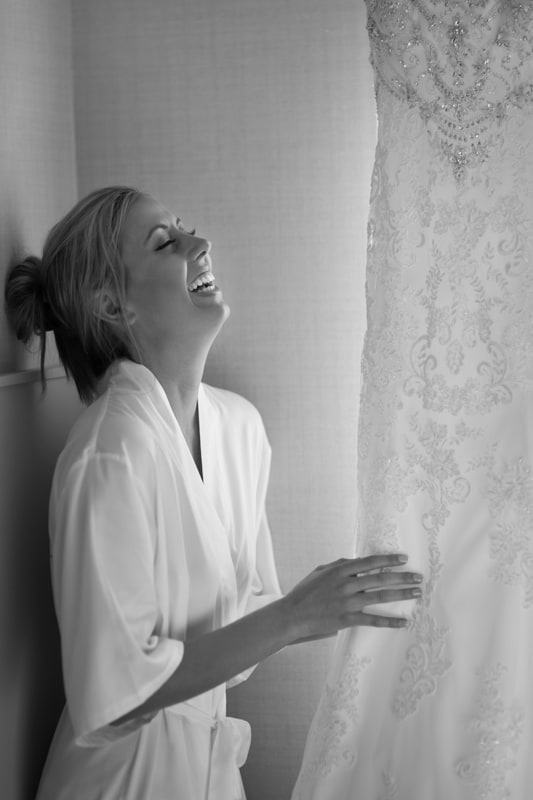 bride looking at wedding dress and laughing