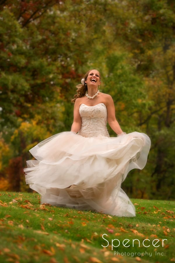 bride laughing amoung fall leaves