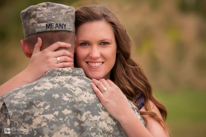 Woman hugging man in army uniform for engagement pictures