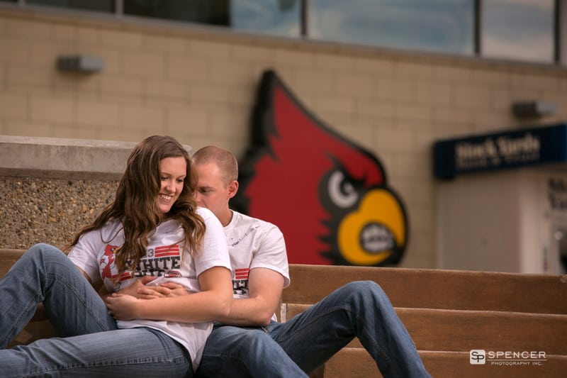 couple kissing for their engagement picture in front of Yum center