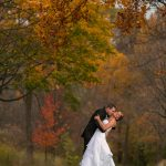 groom kissing bride in front of autumn trees