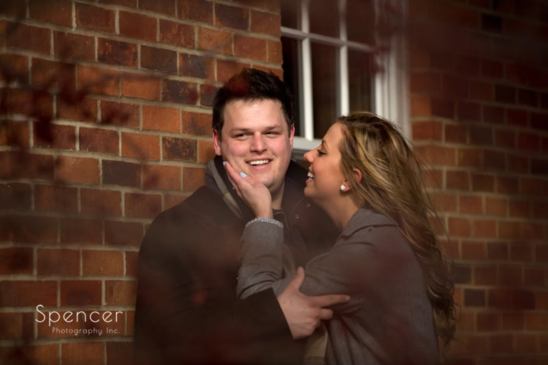 groom smiling into camera while bride touches his cheek