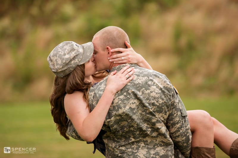 man in army uniform carrying his fiancee