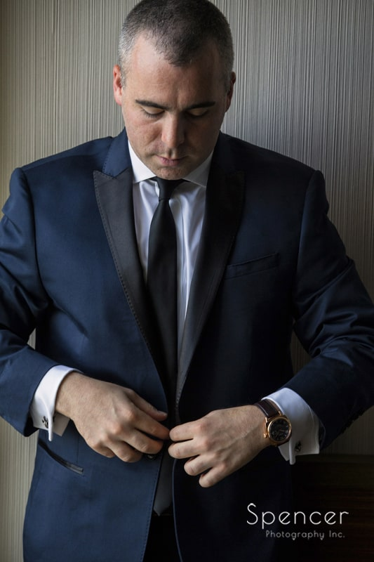 Groom buttons his jacket in suite at Cleveland Westin